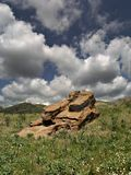 Clouds and rock formation. Solitary red rock against blue sky and clouds Royalty Free Stock Photo
