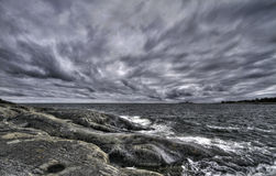 Clouds and rocks. Clouds rolling in over island in Stockholm archipelago stock photos