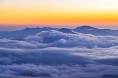 Clouds rolling over the mountains tops at sunrise. Clouds rolling over the mountains tops at orange glow sunrise Royalty Free Stock Images