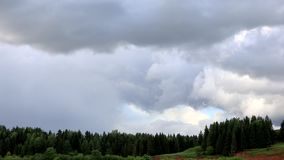 Clouds run across the blue sky. Time lapse. Below the river flows and the forest grows.  stock footage