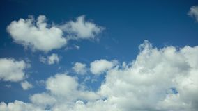Clouds running across the blue sky. 4K timelapse stock footage