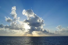 Clouds at Sea. Beautiful sunset at sea in the Western Caribbean. Notice the sun-rays shining on the surface of the ocean Royalty Free Stock Images
