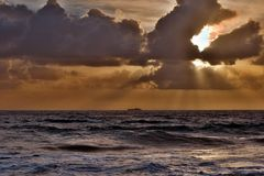 Through clouds on the sea light flows Stock Images