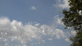 Clouds Seen Through a Waterfall. This is footage of an urban watefall. The clous can be seen moving in the backgorund, and there's a tree to reference the stock video footage