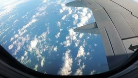 Clouds are Seen through the Window of a Jet Airplane. View from the Airplane Window on a Landscape of Clouds. Airplane flies above the weather stock footage