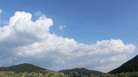 Clouds Shaping over Forested Hills. White clouds are modeled lightly in various forms and shapes, during time lapse,above scenic hills and mountains, on a stock footage