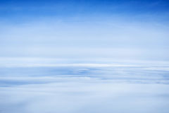 Clouds and sky as seen through window of an aircraft. Stock Image