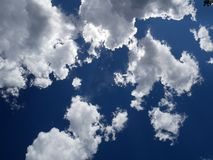 Clouds in sky. Fluffy white clouds floating in the deep blue sky royalty free stock photography