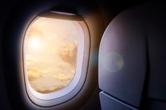 Clouds and sky with golden sunlight and lens flare as seen throu. Gh window of an aircraft Stock Photos