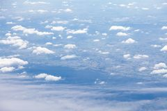 Clouds, sky and ground, looking from the plane. Above, aerial, aeroplane, air, aircraft, airplane, atmosphere, aviation, background, beautiful, beauty, blue stock images