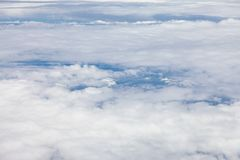Clouds, sky and ground, looking from the plane. Above, aerial, aeroplane, air, aircraft, airplane, atmosphere, aviation, background, beautiful, beauty, blue royalty free stock image
