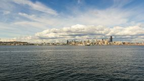 Clouds and sky over Seattle WA city skyline from Alki Beach WA 4k UHD time lapse. Moving white clouds and blue sky over Seattle WA downtown city skyline from stock footage