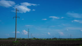Clouds in the sky, rural field plowed earth electricity poles power time period nature tree agriculture clouds sun wind stock video