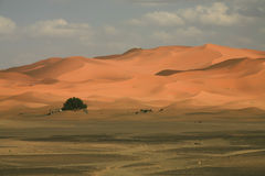 Clouds, Sky, and Soft Pastel Sand Dunes, Edge of Sahara Desert. On the edge of the erg, where flat, sandy soil meets rising hills of sand, the passing clouds in stock image