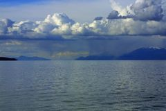 Clouds, sky, water, and mountains. Over the shimmering blue water of the Great Salt Lake near Syracuse, Utah Stock Images