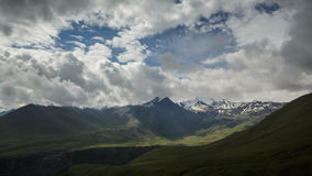 Clouds slowly swim among the Caucasus mountains green and ice scenic peaks in summer sunrise. Sun lights and shadow stock footage