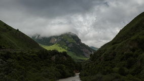 Clouds slowly swim among the mountainous green scenic peaks. A view across the valley and below a rugged mountain river. Shadows from the clouds cover the stock video