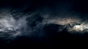 Clouds of smoke against the dark background. Fog, smoke, cloud isolated on a black background.