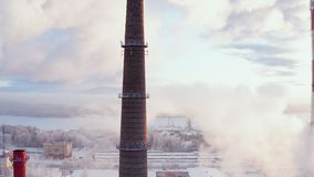 Clouds of smoke rise into the sky from pipe city boiler house. Aerial view. stock video