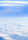 Clouds and smoke Vertical. White fluffy clouds mixed in with white smoke from bushfires below, against a blue sky Stock Image