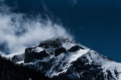 Clouds on snow capped mountain peak Royalty Free Stock Photography