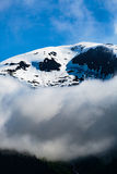 Clouds and Snow Peak. Tracy Arm Fjord, AK, USA - May 27, 2016: Closeup of one of the many mountain peaks seen while cruising the Tracy Arm Fjord, in Alaska. Blue royalty free stock photo
