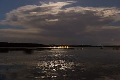 Clouds and stars above lake in the summer night before thunder royalty free stock photo