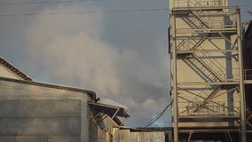 Clouds of steam coming out of the factory buildings, air pollution and energy. stock video footage