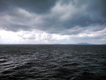 An angry looking black sea. With threatening storm clouds overhead and distant hill on the horizon Royalty Free Stock Image