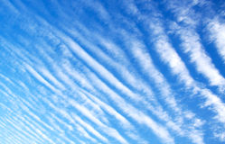 Clouds stripes. Blue sky with sun and interesting composition of clouds - making stripes Stock Image