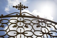 Ornamental wrought-iron gate with cross. Clouds in the summer sky seen through ornamental wrought-iron gate with cross royalty free stock image