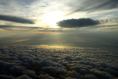 Clouds and Sun Aerial. An in-flight view of the sun shining past two clouds and reflecting off of the cloud layer below stock photography