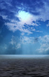 Clouds with sun beams signing through onto sea Stock Images