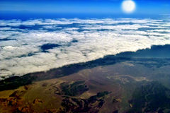 Clouds, sun, earth warming. The blanket of white clouds covered half of the earth below and reflected sunlight. Mountains, field and sea is in shadow. Concept Stock Photo