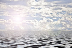 Clouds and sun over water Royalty Free Stock Image