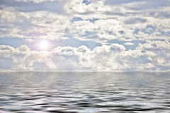 Clouds and sun over water Stock Photography