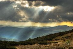 Clouds and sun rays in mountains. Dark clouds and sun rays in mountains. HDR image Royalty Free Stock Images