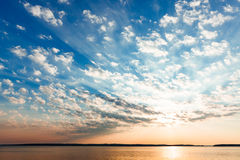 Clouds and sun rays over lake at sunrise Stock Photos