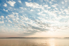 Clouds and sun rays over lake at sunrise Stock Photography