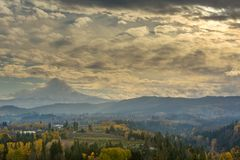 Clouds and sun rays over Mt Hood and Hood River Oregon USA. Rolling clouds over Mount Hood and Sun Rays over Hood River Valley Oregon fruit orchard during fall royalty free stock photography
