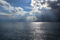 Clouds and sun rays over the sea. Royalty Free Stock Images