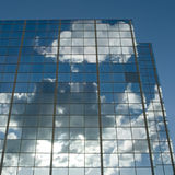 Clouds & sun reflected. In windows of modern office building Royalty Free Stock Images