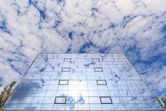 Clouds and sun are reflected in the glasses of windows of a modern building. Bottom view Stock Photos