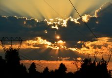 POWER LINES. SUNDOWN BREAKING THROUGH THE CLOUDS Stock Photos