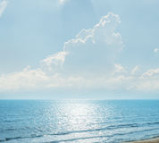 Clouds with sunrays over blue sea Stock Image