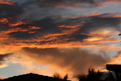 Clouds at sunset. Cumulus clouds over the roofline Stock Photo