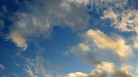 Blue sky with tiny clouds. Clouds in the sunset light against the blue sky stock footage