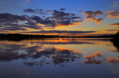 Clouds and sunset reflected in still water Royalty Free Stock Images
