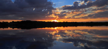Clouds and sunset reflected in the still waters of a lake. Sunset highlighting clouds and reflected in the still waters of Ravensthorpe reservoir Royalty Free Stock Photo