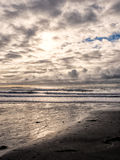 Clouds and surf. A cold winter cloudy sky over the long waves of a sandy beach on the Oregon coast Stock Images